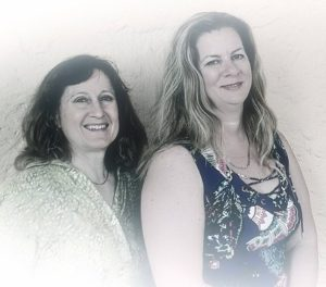 Carol & Carrie Against Wall on Left Side Smiling-428 x 377